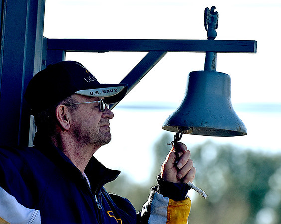 (Brad Davis/The Register-Herald) Silhouetted against the afternoon sky, U.S. Navy veteran Junior Varney rings the bell in memoriam to fellow veterans that have passed on as their names are read aloud during the 5th Annual Healing Fields Ceremony Sunday at the Raleigh County Veterans Museum.