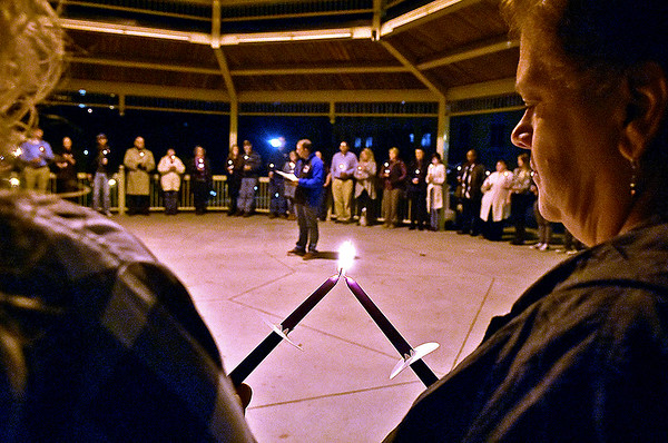 (Brad Davis/The Register-Herald) Attendees help each other light their candles as keynote speaker Matt Bishop (background middle) reads the names of at least 25 victims lost to domestic violence during the closing moments of the Women's Resource Center's 28th Annual candlelight vigil and moment of silence Thursday night under the Word Park gazebo.