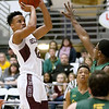 (Brad Davis/The Register-Herald) Woodrow Wilson's Richard Law pulls up for a short-range jumper as Greenbrier East's Zion Jeter defends Saturday night at the Beckley-Raleigh County Convention Center.