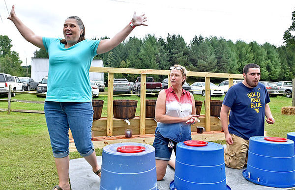 """(Brad Davis/The Register-Herald) Canvas resident Phyllis Elrod, left, reacts after winning the grape eating contest as fellow competitors (from left) Val """"The Grape"""" Homa and Silas Blake are still chewing at the Kirkwood Wine Festival Sunday afternoon in Summersville."""