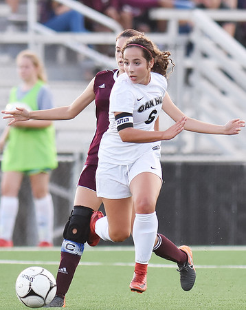 Oak Hill's Georgia White (6) looks to pass after getting past Woodrow's Kyleigh Wyatt (1) during their soccer match Tuesday in Oak Hill. (Chris Jackson/The Register-Herald)