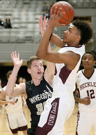 (Brad Davis/The Register-Herald) Woodrow Wilson's Mikey Penn drives to the basket as University's Austin Forbes defends during Big Atlantic Classic action Saturday the Beckley-Raleigh County Convention Center.