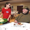 Emerson Young, left, volunteer, serves John Styers, of Beckley, during the Community Christmas Dinner held at The Place in Beckley Moday afternoon.<br /> (Rick Barbero/The Register-Herald)