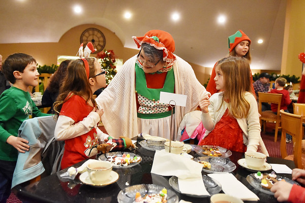 """Mrs. Claus meets with Emily Murphy, 8, and Mandy Fotos, 4, and Eli Fotos, 7, during """"Tea with Santa"""" as part of the Santa Christmas Adventure at The Resort at Glade Springs on Saturday. (Chris Jackson/The Register-Herald)"""