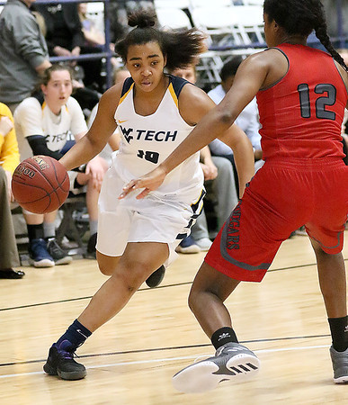 (Brad Davis/The Register-Herald) WVU Tech's Alexandria Gray starts a drive as IU-Kokomo's Whitney Williams defends during the Golden Bears' win over the Cougars Saturday night at the Beckley-Raleigh County Convention Center.