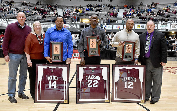 (Brad Davis/The Register-Herald) Woodrow Wilson Boys Basketball Hall of Fame inductees (from left) Brian Kidd (Class of 1990), Kenny Swanson (Class of 1985) and James Harbison (Class of 1987) pose for a quick photo with their new hardware and framed jerseys during the halftime break of the Flying Eagles' game against Greenbrier East Saturday night at the Beckley-Raleigh County Convention Center.