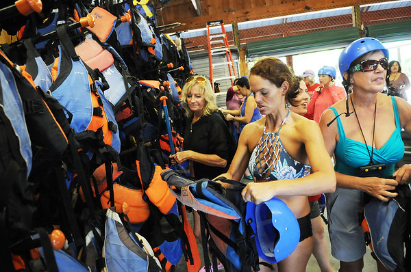 Heather Crutchfield, from Florida, with the Tragedy Assistance Program for Survivors (TAPS), a retreat that welcome families who have lost a loved one as a result of their military service, gets her gear before heading out to whitewater rafter the lower New River art AOTG in Lansing on Friday. (Chris Jackson/The Register-Herald)