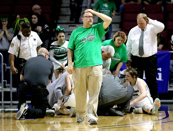 (Brad Davis/The Register-Herald) Wyoming East statistician Tim Lupardus, father of Lady Warriors senior Gabby Lupardus, the injured player being tended to in the background, looks to the sky as he reacts to seeing his daughter suffer an injury for the second time in three years Wednesday afternoon. Gabby would return to the bench to support her teammates.
