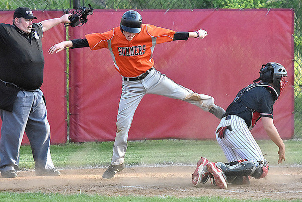 (Brad Davis/The Register-Herald) Summers County baserunner Tucker Lilly catches a cleat on the plate and skips into the air after charging in and dodging Greater Beckley Christian catcher David Wilson tag to score a run off a mishandled pitch Friday evening at Park Middle School.