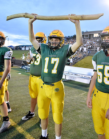 (Brad Davis/The Register-Herald) Greenbrier East's Colton Wickline holds up a piece of drift wood, a bible reference, during every offensive and defensive play as he supports his teammates from the sideline Friday night in Fairlea.