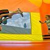 (Brad Davis/The Register-Herald) Seven-year-old Bryce Pittman does flips as four-year-old Peyton Mitchell jumps around with him inside the giant inflatable jumping room during the Kid Quest Carnival Saturday morning in the Marquee Cinemas parking lot. The event featured games, giveaways and appearances by famous movie characters.
