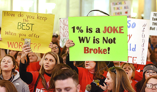Teachers acsross the state hold up sighs during a rally at the State Capitol in Charleston Friday morning the state Senate unanimously passed a bill that would increase teachers and certain state employees salaries by 1 percent.<br /> (Rick Barbero/The Register-Herald)