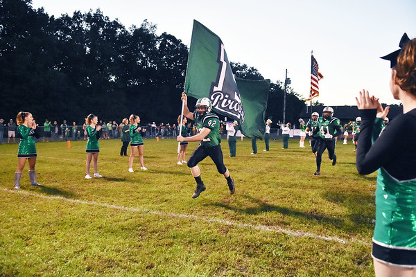 Fayetteville's Sammy Pullens (42) carries the school's flag as he runs onto the field prior to their high school football game against Sherman Friday in Fayetteville. (Chris Jackson/The Register-Herald)