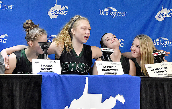 (Brad Davis/The Register-Herald) Wyoming East's Emily Saunders wraps her arms around teammates (from left) Kara Sandy, Katie Daniels and Gabby Lupardus as the group still manages to smile and keep a sense of humor during the postgame press conference despite a loss in the Class AA Girls State Basketball Tournament Saturday afternoon at the Charleston Civic Center.