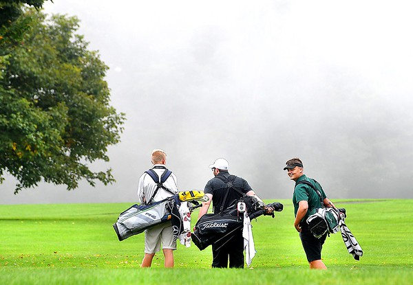 Nathan Daniels, of Shady Springs, left, Dawson Browning, of Westside and Ethan Bradford, of Wyoming East, walk in the fog up the 12th fairway during play in the Class AA Region 3 golf tournament held at Grandview Country Club in Beaver.<br /> (Rick Barbero/The Register-Herald)