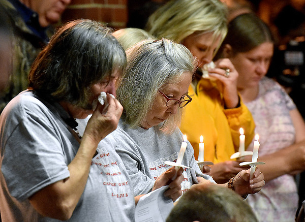 (Brad Davis/The Register-Herald) Friends, family and colleagues of Dr. Luke McElwain hold back tears as they prey near the conclusion of a heavily attended community vigil Wednesday night at the Webster County Memorial Hospital.