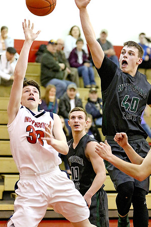 (Brad Davis/The Register-Herald) Independence's Zach Bolen drives to the basket as Wyoming East's Jacob Bishop reaches to block it Friday night in Coal City.