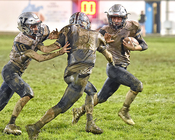 (Brad Davis/The Register-Herald) Valley's Caleb Crisp carries the ball during a muddy slogfest at Meadow Bridge Friday night in Meadow Bridge.