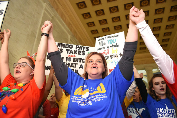 Ashley Jones, teacher Mullens Grade School, left, and Paula Lupardas, service personnel Wyoming East High School, join hands in front of the Senate Chambers floor in the State Capitol rallying during the seventh day of their walkout.<br /> (Rick Barbero/The Register-Herald)