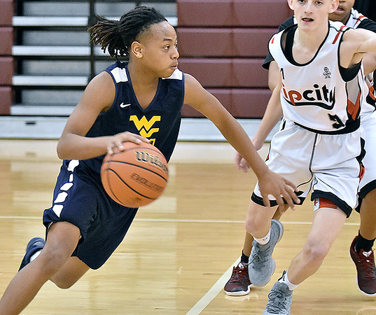 (Brad Davis/The Register-Herald) WV Elite's Jaeon Flack rushes up the court during their eighth grade Biddy Buddy Championship game against VSN Sunday afternoon at Woodrow Wilson High School.