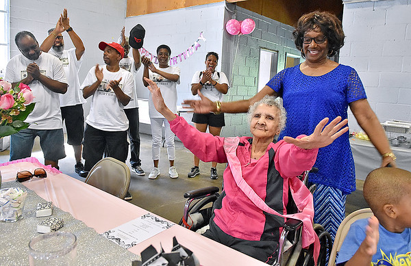 (Brad Davis/The Register-Herald) Friends and family in attendance at left applaud and react as 100-year-old Loretta Shellow, lower right, acknowledges all the kind words and praise during her birthday party along with daughter-in-law Delores Robinson, upper right, and great great grandson Brayden Manns, 3, (out of the frame at lower right) Saturday afternoon at the Maxwell Hill Community Center.