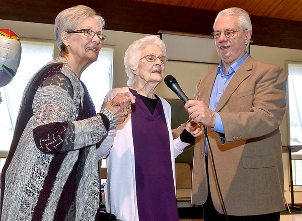 (Brad Davis/The Register-Herald) Ghent resident Florence Mandakunis, middle, thanks the large crowd in attendance for coming out to celebrate with her during the opening moments of her 100th birthday party Saturday afternoon at Calvary Assembly of God. Her son George holds the microphone for her at right while daughter-in-law Lillie Mandakunis helps at left.