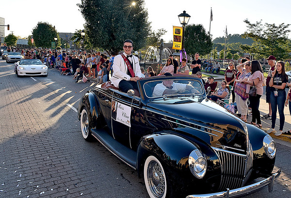 (Brad Davis/The Register-Herald) Prom King candidate Ross Cline, right, and fellow court members roll up Neville Street in style during the school's homecoming parade Wednesday evening in downtown Beckley.