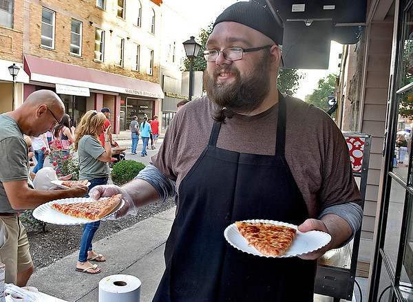 (Brad Davis/The Register-Herald) Roma cook Josh Hudson keeps fresh pizza slices flowing from their booth during Taste of Beckley Saturday evening.