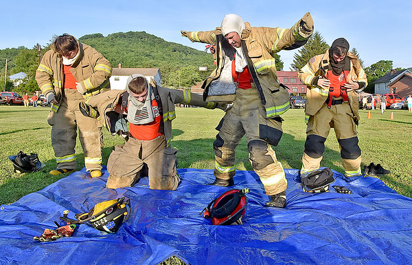 (Brad Davis/The Register-Herald) Firefighters from Talcott Fire Department scramble to get their bunker gear on as fast as possible during the obstacle course portion of the Alderson Fireman's Rodeo Friday evening, part of the town's annual 4th of July Celebration.