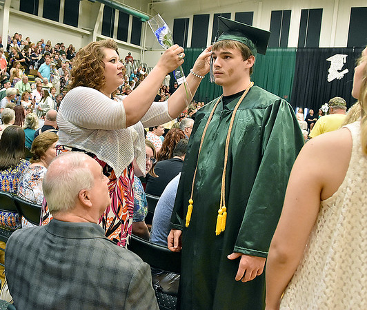 (Brad Davis/The Register-Herald) A graduating Wyoming East senior gets some help untangling his tassel from his mother during the school's 2018 Commencement Ceremony Sunday afternoon in New Richmond.