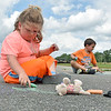 (Brad Davis/The Register-Herald) Young artists Autumn Colombo, left, and Levi Almond draw in chalk on the pavement during Grandview Christian Church's Wacky Wednesday outdoor activity event at their property in Grandview where the old drag strip is.