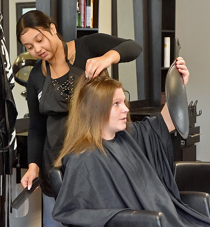 (Brad Davis/The Register-Herald) Customer Amanda Long checks out her look as Get Faded & Dye stylist Tyjhea Grandjean gives her a free haircut Wednesday afternoon.