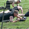 (Brad Davis/The Register-Herald) Spartan racers work their way through low-lying barbed wire obstacles Saturday at the Summit.