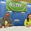 "(Brad Davis/The Register-Herald) New River Community and Technical College President L. Marshall Washington and Active Southern West Virginia Executive Director Melanie Seiler dot the ""i's"" and cross the ""t's"" as they officially put their signatures to an agreement between the two Wednesday afternoon."