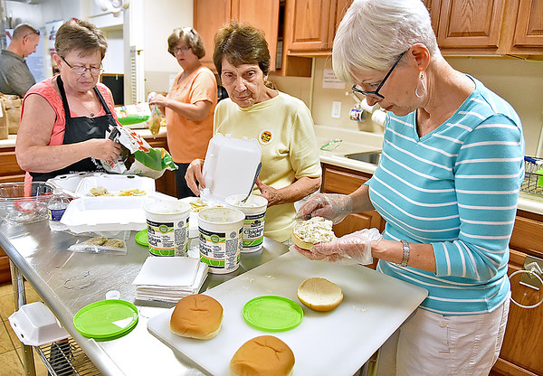 (Brad Davis/The Register-Herald) Church volunteers (from right) Nancy Cales, Phyliss Parker, Susan Goins (background) and Frances Irwin prepare meals for anyone who wanted one during the Brothers & Sisters in Health event Thursday afternoon at First Presbyterian Church in Hinton. The event, sponsored by the church, Summers County ARH and West Virginians for Affordable Health Care, provided medical services to the public free of charge.