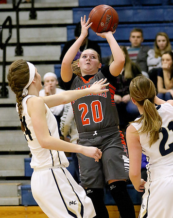 (Brad Davis/The Register-Herald) Summers County's Tiffani Cline drives to the basket as Nicholas County defenders Anna Hamilton, left, Emily Parker, right, step up to defend Wednesday night in Summersville.