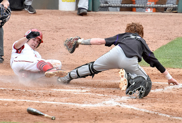 (Brad Davis/The Register-Herald) James Monroe catcher Eli Ballard tags out Bridgeport's Ryan Goff, one of a handful of clutch putouts at the plate, Friday afternoon at Appalachian Power Park in Charleston.