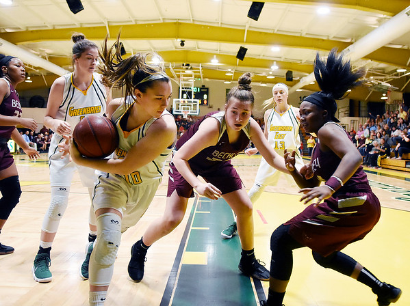 Greenbrier East's Abby Bartenslager (10) grabs a rebound over Woodrow's Laken Ball (30) and Tyjere Underwood (10) during the first half of their basketball sectional championship game in Lewisburg Friday. (Chris Jackson/The Register-Herald)