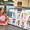 (Brad Davis/The Register-Herald) Chocolate Moose owner Kevin Traube holds and employee Emily Covey pose for a quick photo at the local coffee shop's new Raleigh General Hospital location, which opens Monday, Friday afternoon. Artist Hunter Warden created the various moose illustrations on their menu board.
