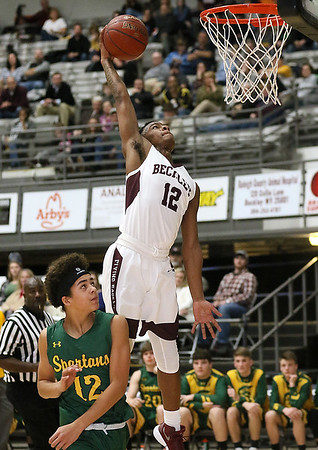 (Brad Davis/The Register-Herald) Woodrow Wilson's Ty Walton goes up for a dunk as Greenbrier East's Steven Winnings can only watch Saturday night at the Beckley-Raleigh County Convention Center.