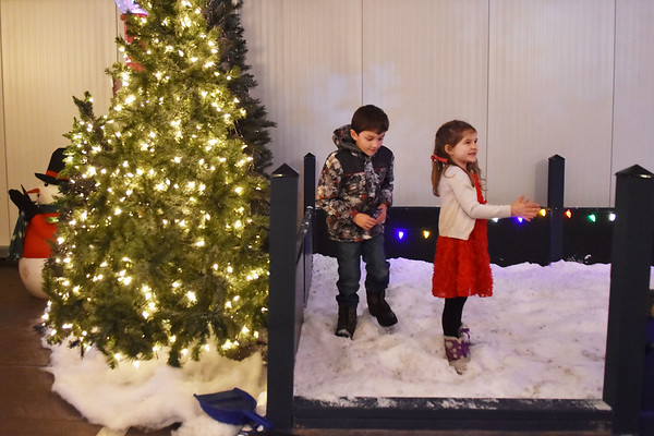 Eli Fotos, 7, and his sister, Mandy Fotos, 4, play in artificial snow during the Santa Christmas Adventure at The Resort at Glade Springs on Saturday. (Chris Jackson/The Register-Herald)