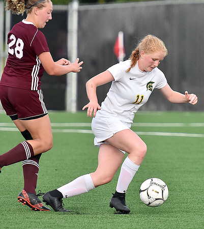 (Brad Davis/The Register-Herald) Greenbrier East's Kate Perkins gets by Woodrow Wilson's Colby Agnor Friday evening at the YMCA Paul Cline Memorial Soccer Complex.