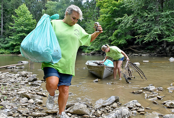 (Brad Davis/The Register-Herald) Volunteers Lisa Snodgrass, left, and Amanda Lemon work to clean up a section of the Peach Tree Creek and falls area during a cleanup project Saturday afternoon near Naoma.