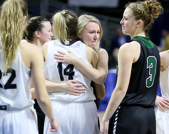 (Brad Davis/The Register-Herald) Wyoming East senior Gabby Lupardus is hugged and congratulated on a great career by the North Marion basketball team after being put in the game late in the Lady Warriors Class AA State Championship game loss to the Lady Huskies Saturday afternoon at the Charleston Civic Center. Coach Angie Boninsegna subbed Lupardus in so a North Marion player could foul her, sending her to the free throw line in a symbolic gesture for one final point to cap her career. Lupardus made the free throw. Fellow senior Kara Sandy looks on at right.