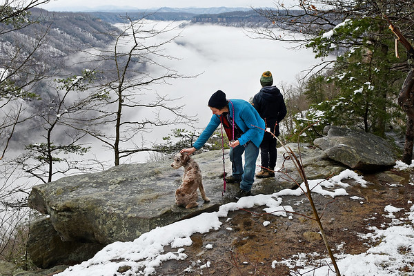 """Anthony Vargo, left, pets his dog """"Rosie"""", as Claire Lehotsky, both living in Oak Hill, looks out at fog lingering in the New River Gorge on Beauty Mountain Trail on Monday. (Chris Jackson/The Register-Herald)"""