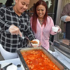 (Brad Davis/The Register-Herald) Roma's Kelley Lim, right, and Tamya Hite prepare bowls of rice and butter chicken during Taste of Beckley Saturday evening.