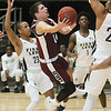 (Brad Davis/The Register-Herald) Woodrow Wilson's Bryce Radford drives and scores through First Love defenders Isiaiah Wilson, left, and JaMier Fletcher during the Little General Battle for the Armory championship game Saturday night at Beckley-Raleigh County Convention Center.
