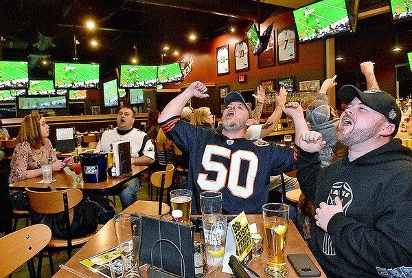 (Brad Davis/The Register-Herald) Princeton residents Raymond Hall, far right, and his cousin Michael, left of Raymond, react to events on the field along with Patriots fans and Beckley residents Matt Workman and his wife Jolene (left) as they watch the Super Bowl at Buffalo Wild Wings Sunday night. The Halls are originally from Chicago, which explains Michael's Bears jersey.