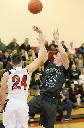(Brad Davis/The Register-Herald) Wyoming East's McQuade Canada shoots from three-point range as Independence's Jared Cannady defends Friday night in Coal City.