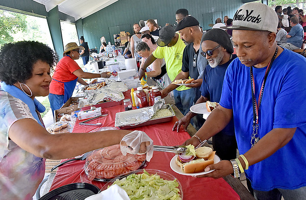 (Brad Davis/The Register-Herald) Hungry guests load their plates with grillin' food as they work their way along the table during the 14th Annual Juneteenth Community Cookout Sunday afternoon at New River Park, capping off a week of activities celebrating 152 years since the end of slavery.
